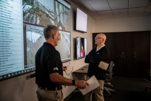 Campus Officers watching security footage on large television